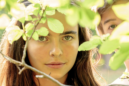 Portrait couple: portrait of two teenagers behind some leaves