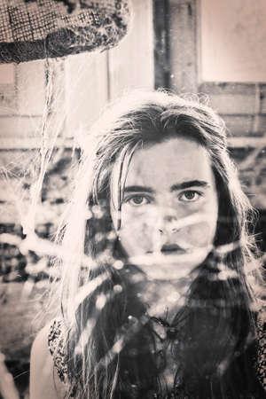 vintage shot of a teenage girl behind a spider web
