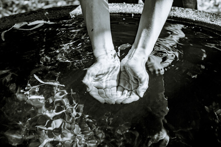 Holding water from a well  in cupped hands, black and white shot Stock Photo