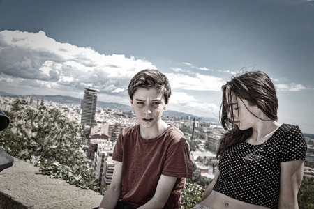 mutually: siblings sitting on a wall with Barcelona in background