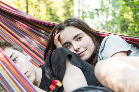 close up of two siblings laying in a hammock