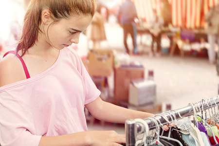 specific clothing: teenage girl looking for clothes at a flea market