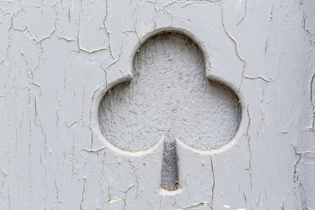flaws: old grungy shamrock sign shaped in a wood wall