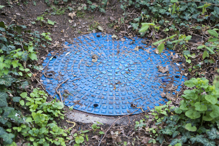 sprayed: round blue sprayed sewer cover in the dirt