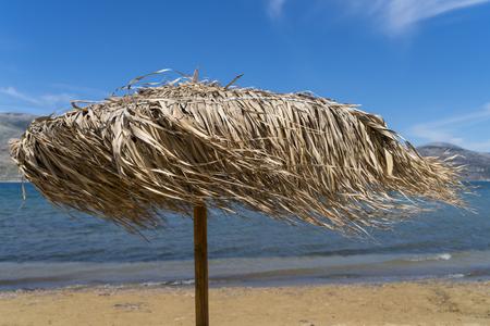 Straw parasol, windy day on the beach