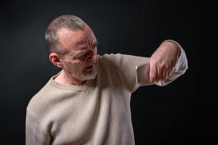 desperate old man shaking his smart phone Stock Photo