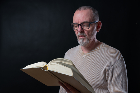 old man with glasses reading a book Stock Photo