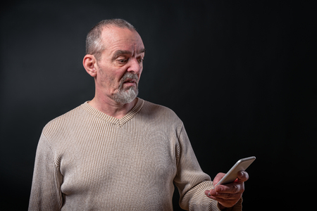 old man dont understand his smart phone Stock Photo