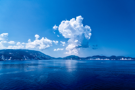 ocean landscape with mountain range and dramatic clouds