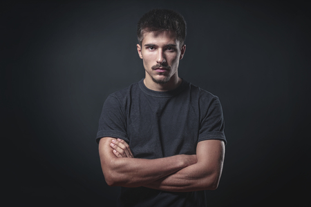 portrait of a strong young man with black background