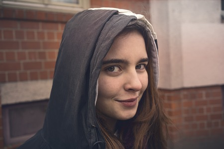 portrait of a smiling young woman with parka