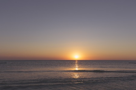 sunset over the horizon of the ocean with cloudless sky Imagens