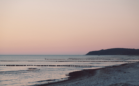 sunset over the beach with rows of groins in the sea