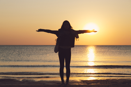 silhouette of a woman on a beach with stretched arms, setting sun on her hand
