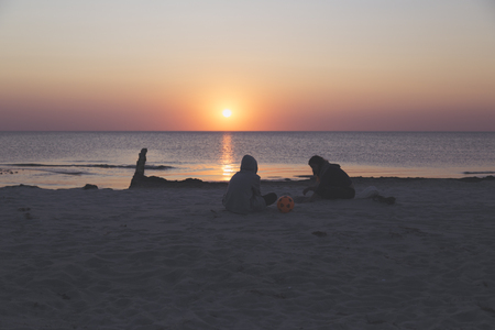 sunset over the sea, tow teens sitting on the beach