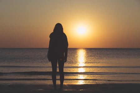 sunset over the sea, silhouette of a woman standing on the beach