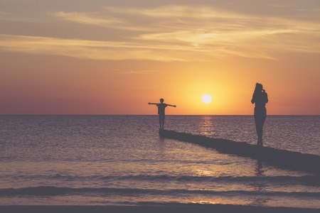 sunset over the baltic sea, two teens are balancing on a groin