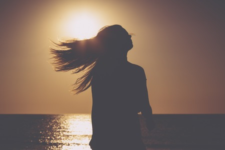 sunset on a beach, silhouette of a woman with flying hair Imagens