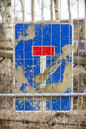 dirty german dead end traffic sign,behind a metal fence Stock Photo