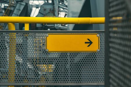 industrial facility, yellow empty direction sign with black arrow