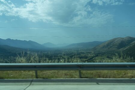 Landscape with mountains and guardrail photographed from a moving car