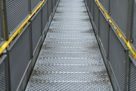 Pedestrian bridge of metal in an industrial facility with yellow railings Stok Fotoğraf
