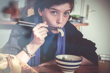 boy is eating asian food with chopsticks Stok Fotoğraf