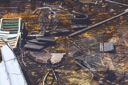 Old shopping trolleys and other garbage in a small pond