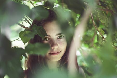 portrait of a young smiling woman covered of blurred leaves Stock Photo