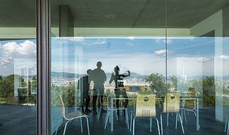 Barcelona mirroring in a window with three persons 스톡 콘텐츠
