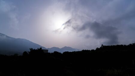 silhouette of a landscape with mountains on a misty day