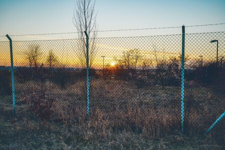 sunset behind a metal fence with barbwire