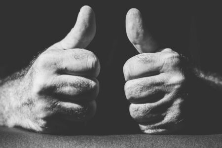 close-up of two hands showing their thumbs up Banco de Imagens