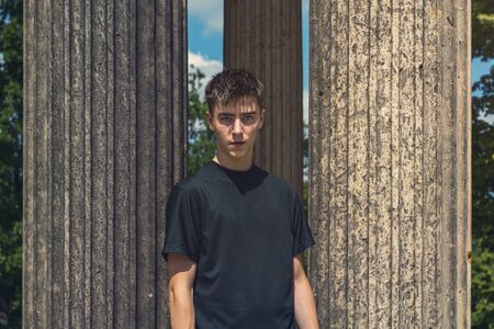portrait of a young man standing between ancient columns