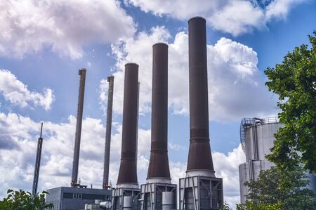 three large chimneys of a power plant with a beautiful cloudy sky Banco de Imagens