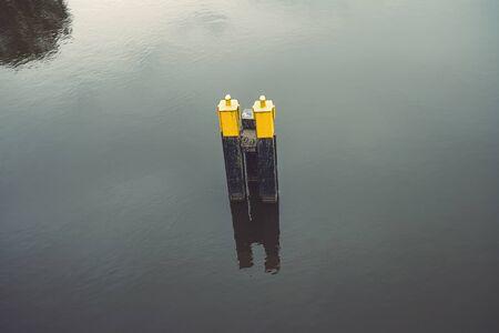 single yellow black mooring post in water