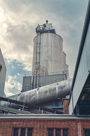three silos and a large pipe of a factory with dramatic sky