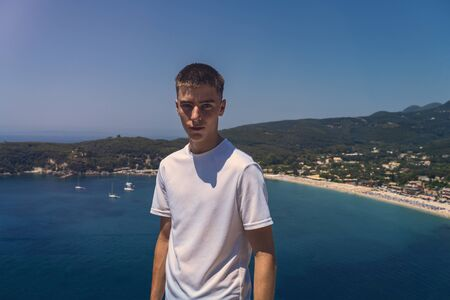 portrait of a self-confident young man with the beach of the city of parga in the background