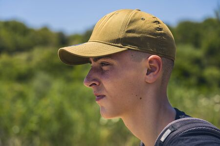 portrait of a young man with base cap in profile