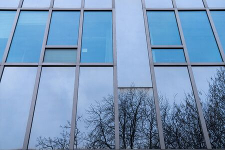 blue glass facade with mirroring trees