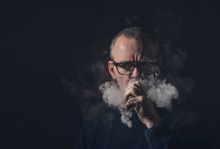 studio portrait of a man with vaporiser and glasses 写真素材