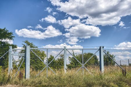 blue metal fence gate with barb wire in a landscape