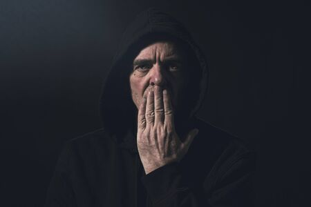 portrait of a man with a hoodie holding a hand in front of his mouth Stockfoto