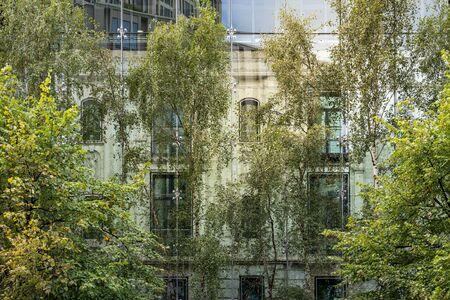 old house behind a modern glass facade with trees in foreground