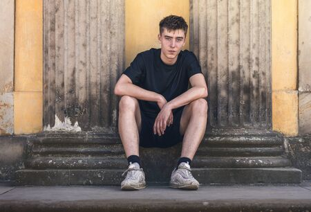 portrait of a young man sitting between two ancient pillars Stockfoto