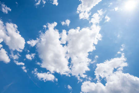 blue sky with clouds and sun, photographed upwards for backgrounds