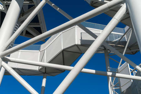 Section of a white observation tower with blue sky in the background