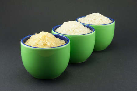Three varieties of rice in three small green cups photo