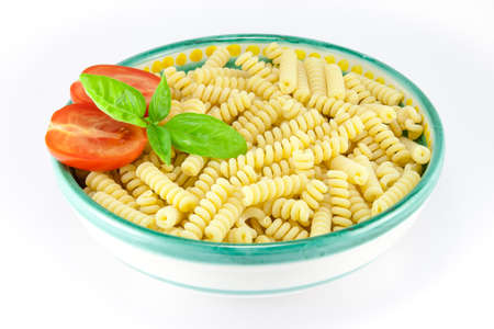 Bowl full of fusilli pasta with tomatoes and basil photo