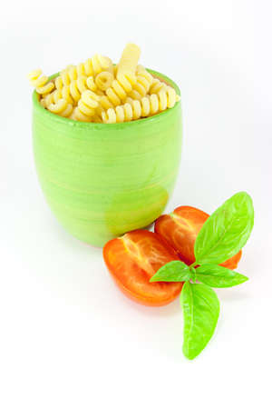 Fusilli pasta in a green jar with tomatoes and basil photo